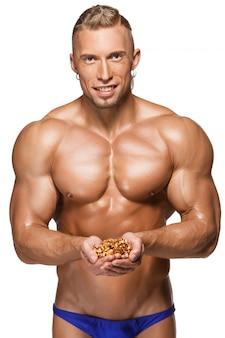 Kształtujący i zdrowy ciało mężczyzna trzyma orzechy włoskie