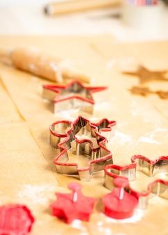 Kształty czerwonego imbiru i ciasta na brązowym papierze do pieczenia. przygotowuję się do świąt.
