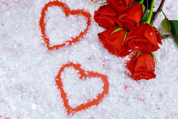 Kształty serca na błyszczącym śniegu i pięknych czerwonych różach. walentynki.