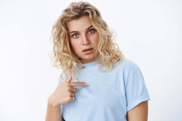 Kto ja. portret przesłuchiwanej i zszokowanej kobiety wskazuje na siebie trzymającą palec na klatce piersiowej i szeroko otwiera oczy ze zdziwienia, gdy jest wybierana lub oskarżona, stojąc zdumiona i zdezorientowana nad białą ścianą