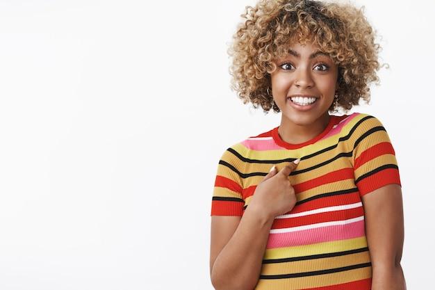 Kto ja. portret zaskoczonej, uroczej i beztroskiej, uroczej afroamerykańskiej dziewczyny wskazującej na przesłuchiwaną i podekscytowaną siebie jako wspomnianą lub wybraną, uśmiechającą się szeroko, pozującą na białej ścianie