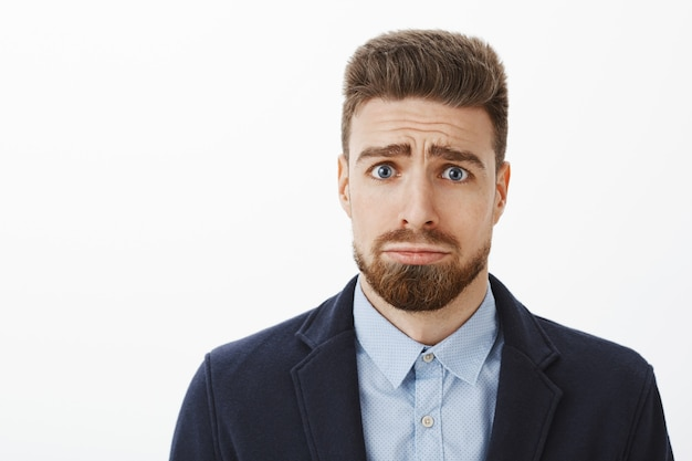 Kto może odrzucić tę ślicznotkę z niebieskimi oczami. uroczy przystojny i charyzmatyczny chłopak z brodą i chorymi brwiami marszczy brwi, robiąc głupią i uroczą minę, prosząc o przysługę lub przepraszając
