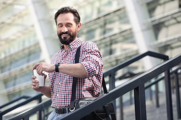 Która godzina. wesoły mężczyzna broda sprawdzanie czasu podczas picia kawy na świeżym powietrzu