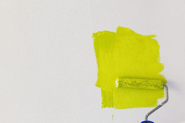 Ktoś malował białą ścianę w rozświetlającym żółtym kolorze