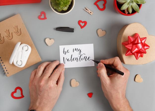 Ktoś pisze kartkę be my valentine obok pudełka z prezentami i serduszek na szarym widoku z blatu