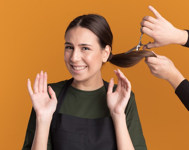 Ktoś tnie warkocz nożyczkami do przerzedzania włosów niezadowolonej młodej brunetki fryzjerki w mundurze stojącym z uniesionymi rękami odizolowanymi na pomarańczowej ścianie z kopią przestrzeni