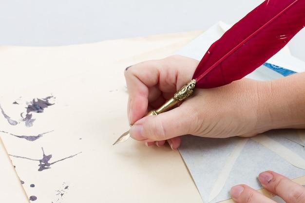 Ktoś trzyma rękę z czerwonym piórem na starych dokumentach