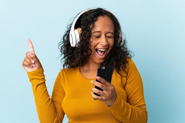 Kubańska dziewczyna nastolatka na białym tle na niebieskim tle słuchania muzyki z telefonu komórkowego i śpiewu