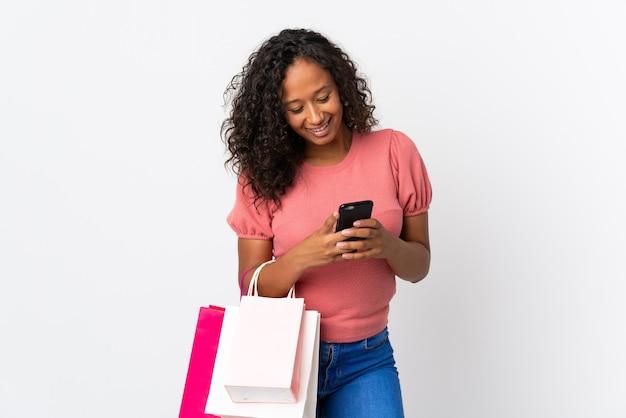 Kubańska dziewczyna nastolatka na białym tle trzymając torby na zakupy i pisanie wiadomości z jej telefonu komórkowego do przyjaciela