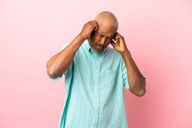 Kubański senior na różowym tle sfrustrowany i zakrywający uszy