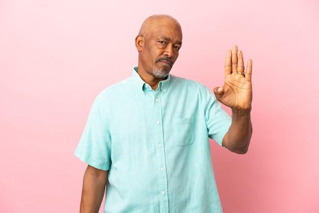 Kubański senior odizolowany na różowej powierzchni, wykonując gest zatrzymania i rozczarowany