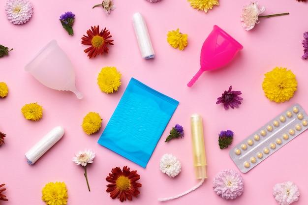Kubeczek menstruacyjny, doustne środki antykoncepcyjne i tampony medyczne z kwiatami na zdjęciu z góry