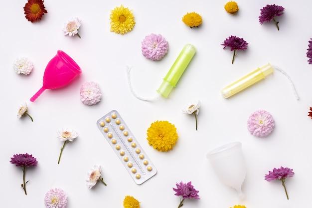 Kubeczek menstruacyjny, doustne środki antykoncepcyjne i tampony medyczne z widokiem z góry kwiatów