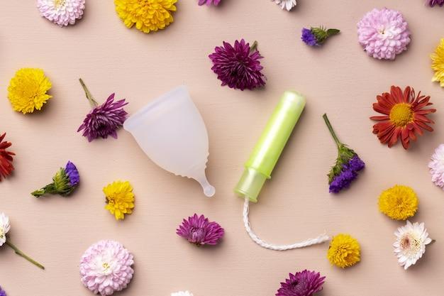 Kubeczek menstruacyjny i tampony na tle kwiatowy wzór
