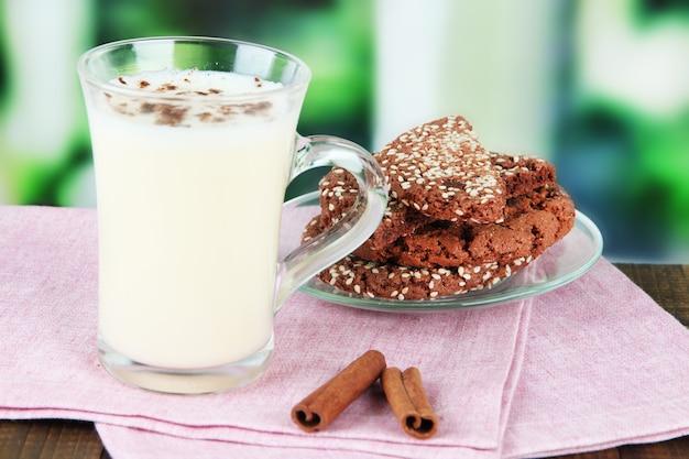 Kubek ajerkoniaku z cynamonem i ciasteczkami na stole na jasnym tle