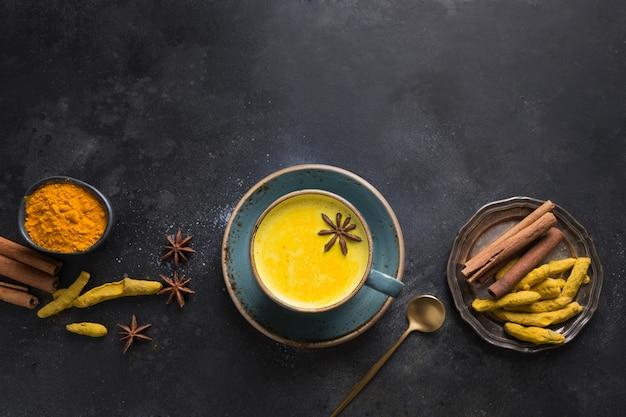 Kubek ajurwedyjskiego złotego mleka kurkumowego z proszkiem kurkumy i gwiazdą anyżu na czarnym tle. widok z góry.
