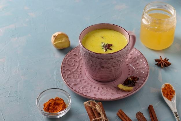 Kubek ajurwedyjskiego złotego mleka z kurkumy latte z kurkumą w proszku, cynamonem, imbirem i anyżem na jasnoniebieskiej powierzchni, miejsce