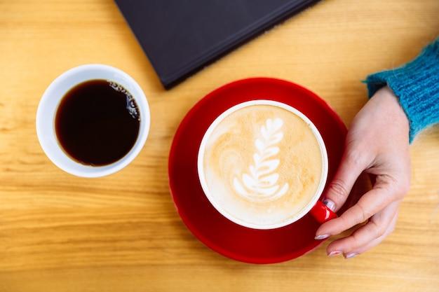 Kubek aromatycznej kawy cappuccino w kobiecej dłoni na stole obok książki