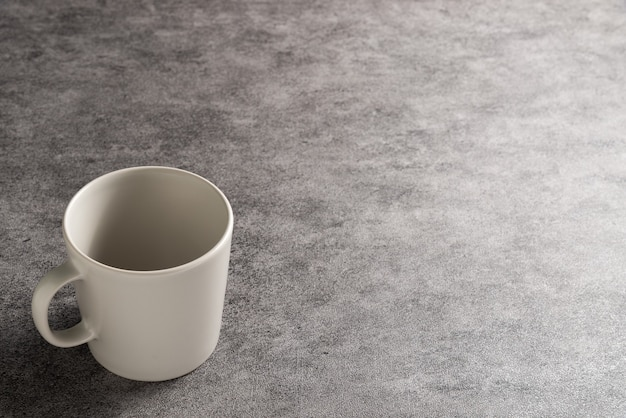 Kubek biały kawy na szarym tle kamienia z miejsca kopiowania.