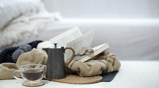 Kubek, czajnik i książka na pierwszym planie w zimnych kolorach na rozmytym tle.