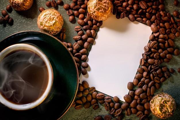Kubek czarnej gorącej aromatycznej kawy na stole, czekoladki, ziarna kawy rozrzucone po tle