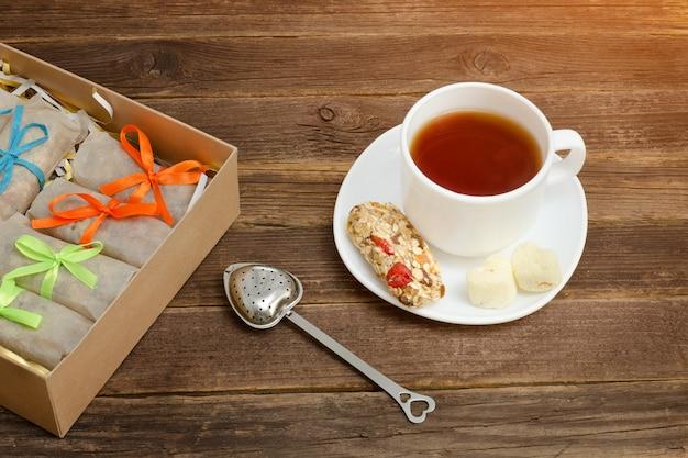 Kubek czarnej herbaty, baton musli i pudełka z batonikami