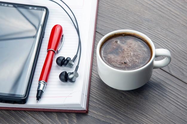 Kubek czarnej kawy, długopis, telefon komórkowy, notatnik i słuchawki są na stole. biznesowe artykuły biurowe.