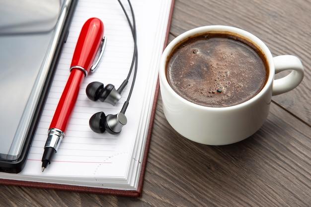 Kubek czarnej kawy, długopis, telefon komórkowy, notatnik i słuchawki są na stole