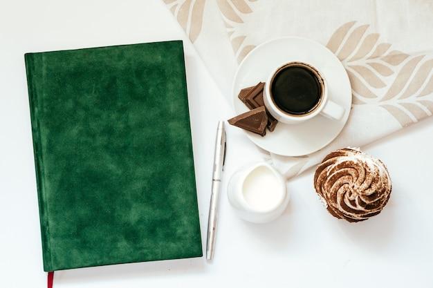 Kubek czarnej kawy z czekoladą i babeczkami oraz zielony notatnik
