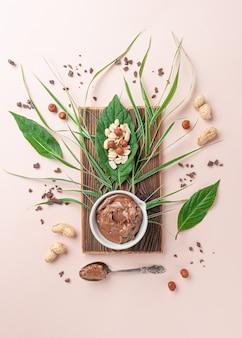 Kubek czekoladowego masła orzechowego i orzechów laskowych. na drewnianej desce teksturowanej.