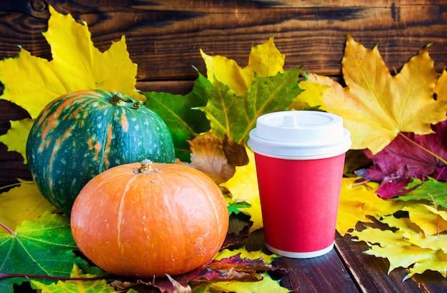 Kubek czerwonej kawy na wynos z liśćmi marple i dyniami