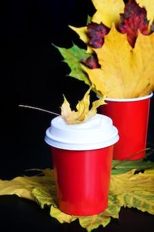 Kubek czerwonej kawy na wynos z marple leafon czarny. jesienny nastrój