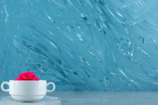 Kubek czerwonej kiszonej kapusty na niebieskim stole.