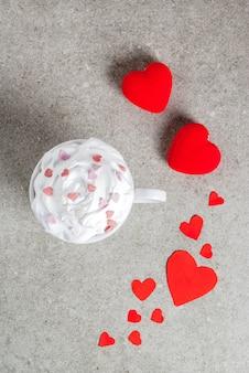 Kubek do gorącej czekolady, z bitą śmietaną i słodkimi sercami, z dwoma pluszowymi czerwonymi sercami