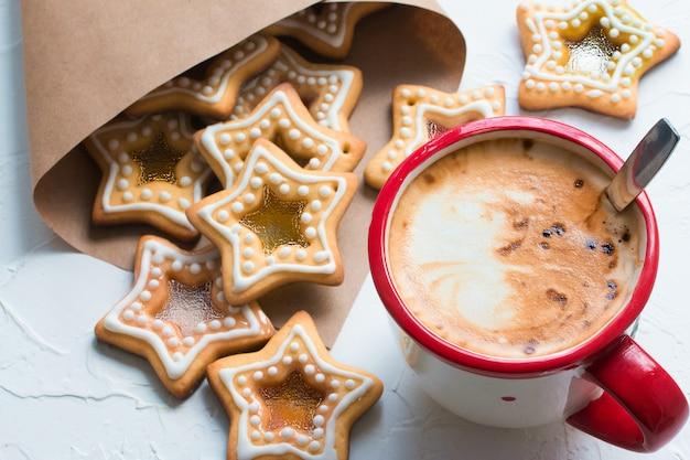 Kubek do kawy na białym stole z domowymi ciasteczkami świątecznymi w kształcie cukrowych karmelowych gwiazdek