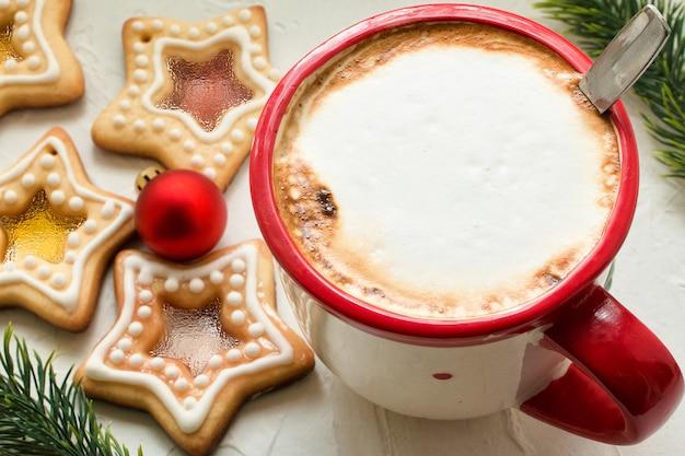 Kubek do kawy na stole z domowymi ciasteczkami świątecznymi w kształcie cukrowych karmelowych gwiazdek