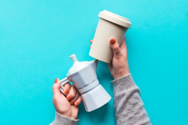 Kubek do kawy wielokrotnego użytku lub trzymaj kubek i biały ceramiczny ekspres do kawy w rękach kobiety na jasnoniebieskiej ścianie mięty. kreatywne mieszkanie, widok z góry, modna koncepcja zero odpadów z filiżankami wielokrotnego użytku.