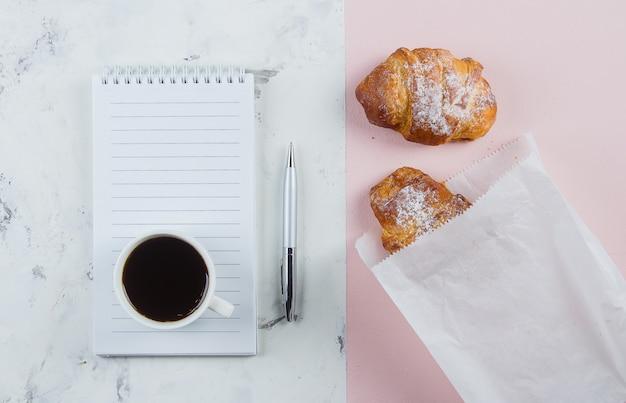 Kubek do kawy z rogalikami i pustym notatnikiem i piórem do biznesplanu i pomysłów na projekt