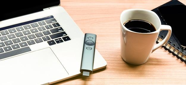 Kubek do kawy z widokiem z góry i laptop na stole w sali konferencyjnej