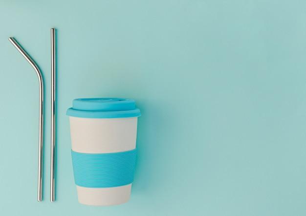 Kubek ekologiczny wielokrotnego użytku i metalowe słomki do picia na niebieskim tle.