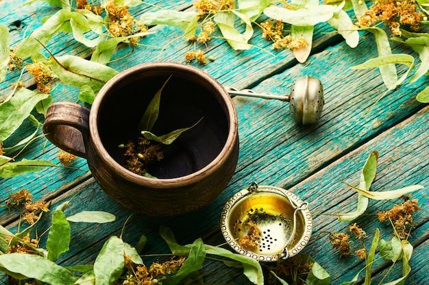 Kubek gliniany i świeże liście i kwiatostany lipy. ziołolecznictwo i homeopatia. rośliny lecznicze.
