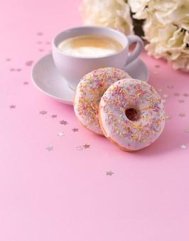 Kubek gorącego cappuccino i dwa pączki z kwiatami na różowo