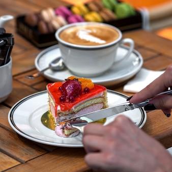 Kubek gorącego cappuccino z deserem z gąbki pokrytym syropem jagodowym