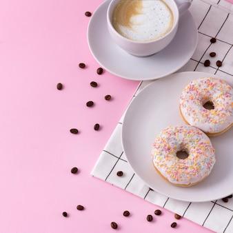 Kubek gorącego cappuccino z dwoma pączkami na różowo