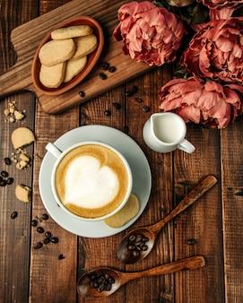 Kubek gorącego cappuccino z kruche ciasteczka
