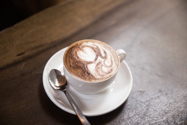 Kubek gorącego cappucino leży na drewnianym stole. to sztuka na latte.