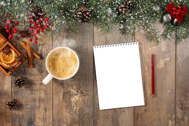 Kubek gorącego kakao lub czekolady, ozdoby świąteczne i notatnik z listą rzeczy do zrobienia na drewnianym stole vintage