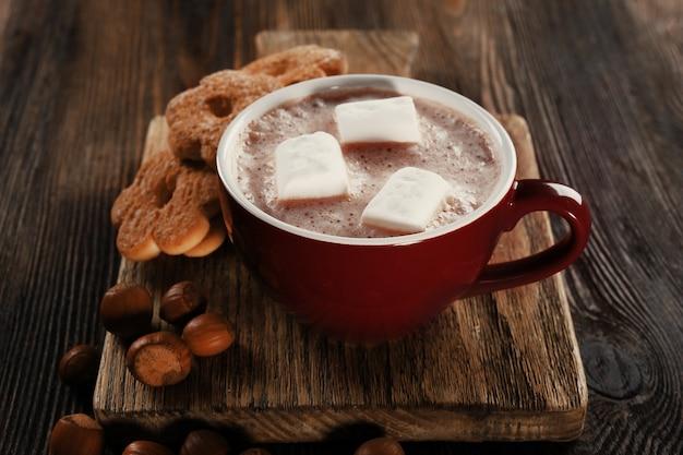 Kubek gorącego kakao z ciasteczkami i orzechami na drewnianej desce kuchennej, z bliska