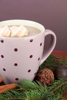 Kubek gorącego kakao z czekoladkami i gałązkami jodłowymi na stole na ciemnym tle