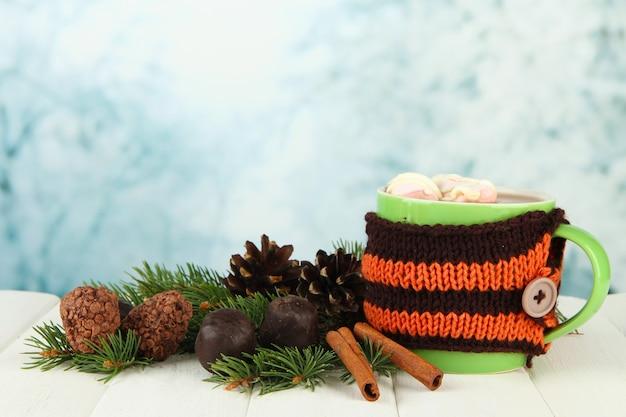Kubek gorącego kakao z czekoladkami i gałązkami jodłowymi na stole na jasnym tle